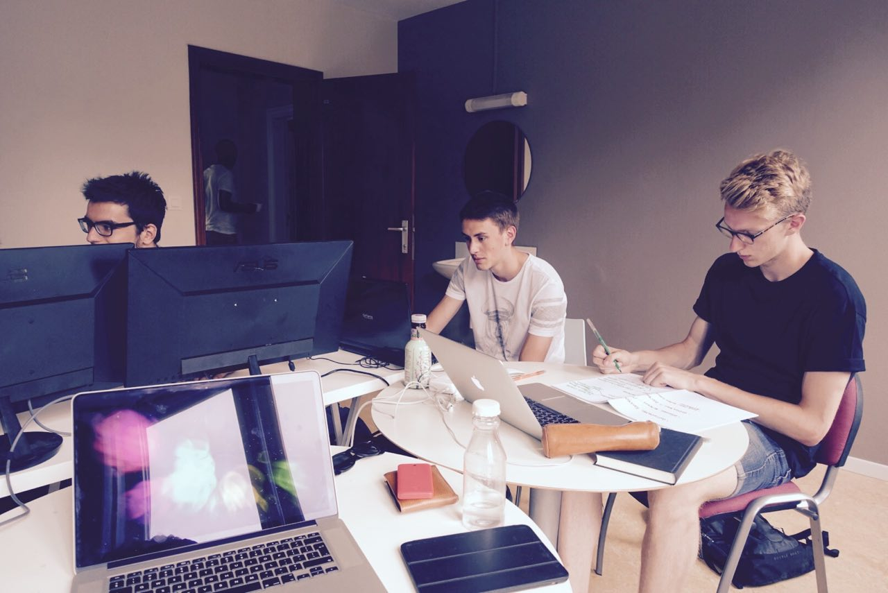 Three students sitting in front of their computer in a room at open Summer of code 2015